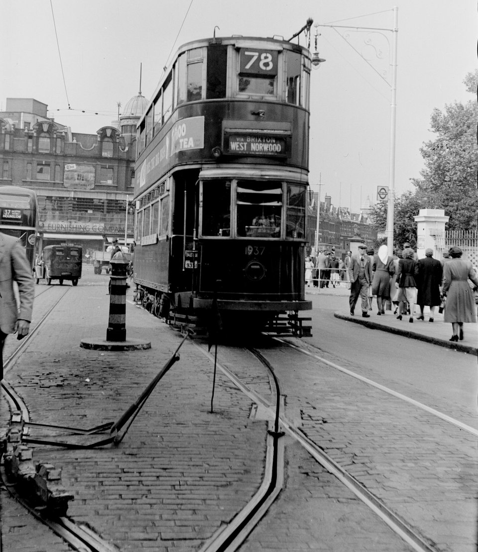 the point at which a tram driver would 'shoot the plough' and raise the trolley pole on leaving a conduit section of track. Tramcar 1937 at Effra Road, Brixton. H.B. Priestley, 21/5/1949.